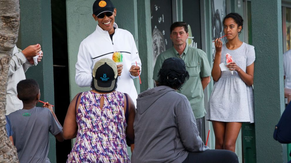 President Barack Obama eats shave ice with daughter Malia, at right, at Island Snow, Jan. 1, 2015, in Kailua, in Hawaii during the Obama family vacation.