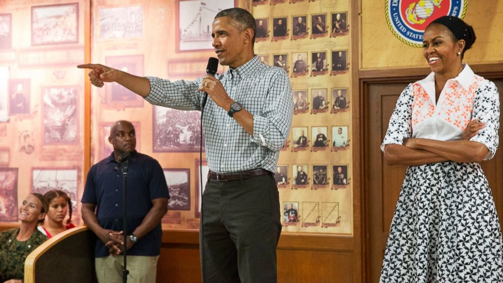 President Barack Obama, with first lady Michelle Obama, points toward a child in the audience as he greets troops and their families on Christmas Day, Dec. 25, 2014, at Marine Corps Base Hawaii in Kaneohe Bay, Hawaii.