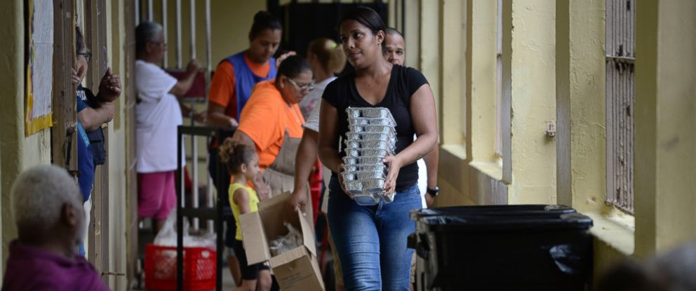 A woman passes out trays of food to evacuees taking shelter at the Juan Ponce de Leon Elementary School before the arrival of Hurricane Maria, in Humacao, Puerto Rico, Tuesday, Sept. 19.