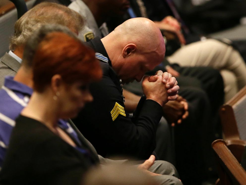 PHOTO: A police officer bows his head during the funeral for Dallas Police Sr. Cpl. Lorne Ahrens at Baptist Church in Plano, Texas, July 13, 2016.