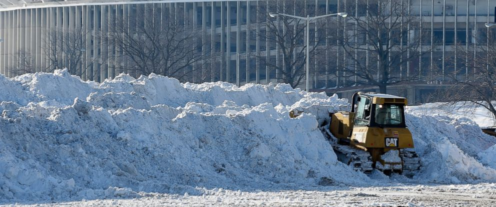 PHOTO: A vehicle pushes up piles of snow after trucks dump their loads of snow in the parking lots of RFK Stadium in Washington, Jan. 25, 2016, as the nations capital digs out following a monster weekend snow.