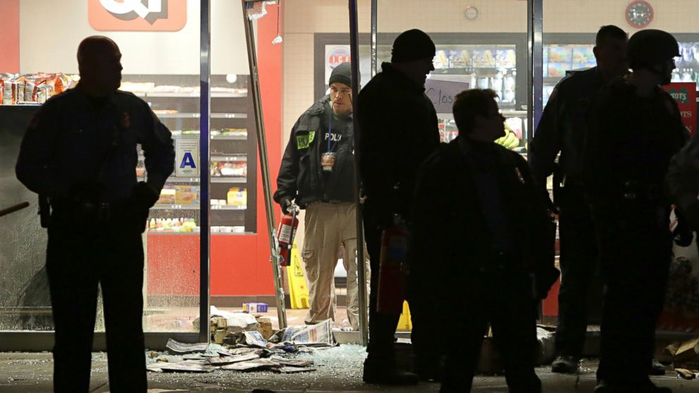 A police officer with a fire extinguisher stands in the broken out entry to a QuikTrip, Dec. 24, 2014, following a shooting nearby in Berkeley, Mo.