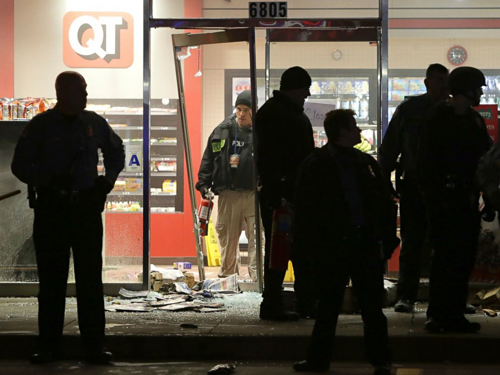PHOTO: A police officer with a fire extinguisher stands in the broken out entry to a QuikTrip, Dec. 24, 2014, following a shooting nearby in Berkeley, Mo.