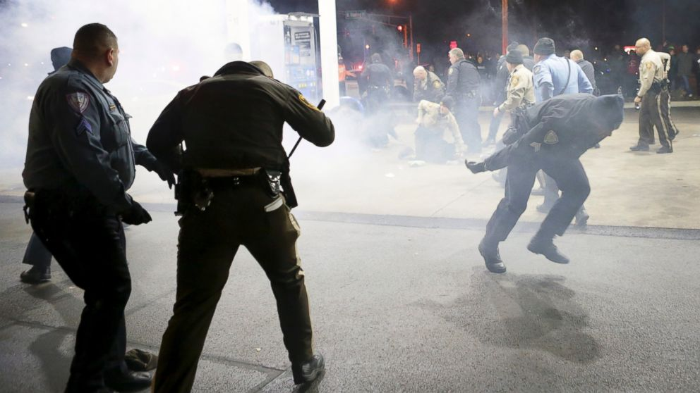Police try to control a crowd, Dec. 24, 2014, on the lot of a gas station following a shooting in Berkeley, Mo.
