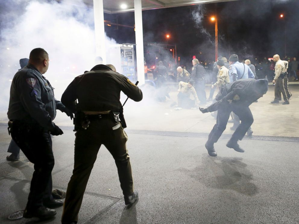 PHOTO: Police try to control a crowd, Dec. 24, 2014, on the lot of a gas station following a shooting in Berkeley, Mo.