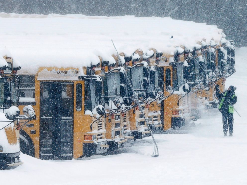 PHOTO: A driver cleans snow off school buses in Derry, N.H., Feb. 2, 2015.