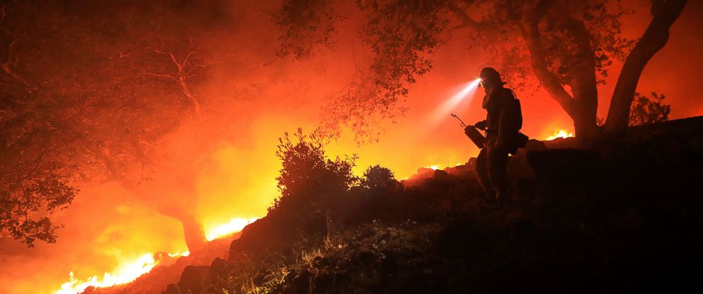 A San Diego Cal Fire firefighter monitors a flare up on a the head of a wildfire (the Southern LNU Complex), off of High Road above the Sonoma Valley, Wednesday Oct. 11, 2017, in Sonoma, Calif.