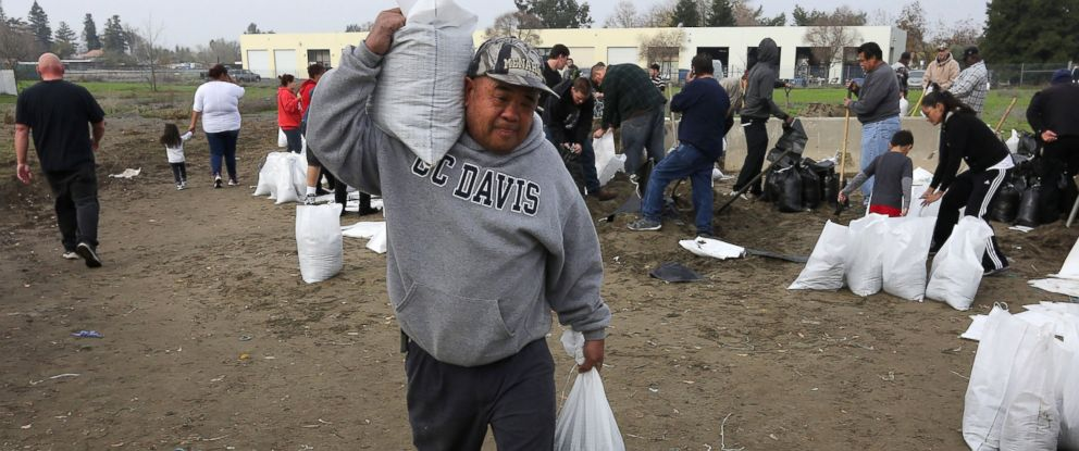 PHOTO: Sam Taing carries sandbags to his pickup truck to be placed around his home in the Sacramento suburb of North Highlands, Calif., Dec. 10, 2014.