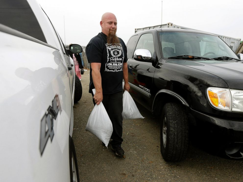 PHOTO: Carl Corbin carries sandbags to his vehicle to be placed around the home of an elderly couple he lives near in the Sacramento suburb of North Highlands, Calif., Dec. 10, 2014.