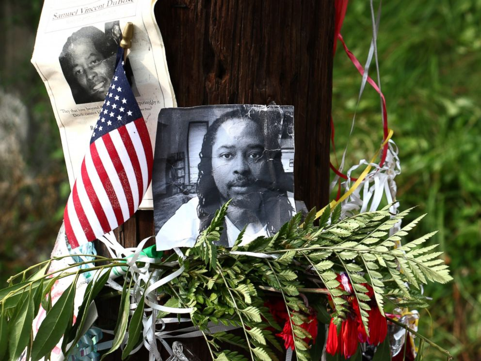Photos of Samuel DuBose hang on a pole at a memorial, July 29, 2015, in Cincinnati, near where he was shot and killed by a police office. Murder and manslaughter charges were announced against Ray Tensing for the shooting death of DuBose.