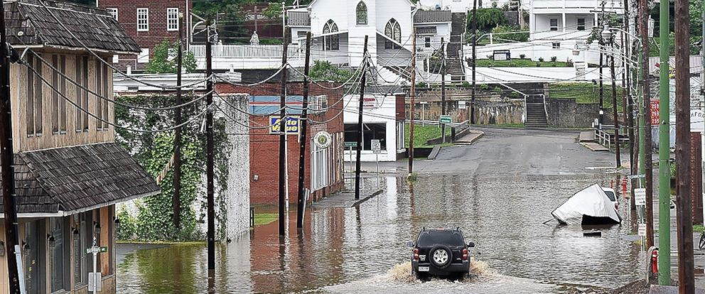 PHOTO: A vehicle makes a wake along the flooded Lower Oakford Ave., June 24, 2016, in Richwood, W.Va.