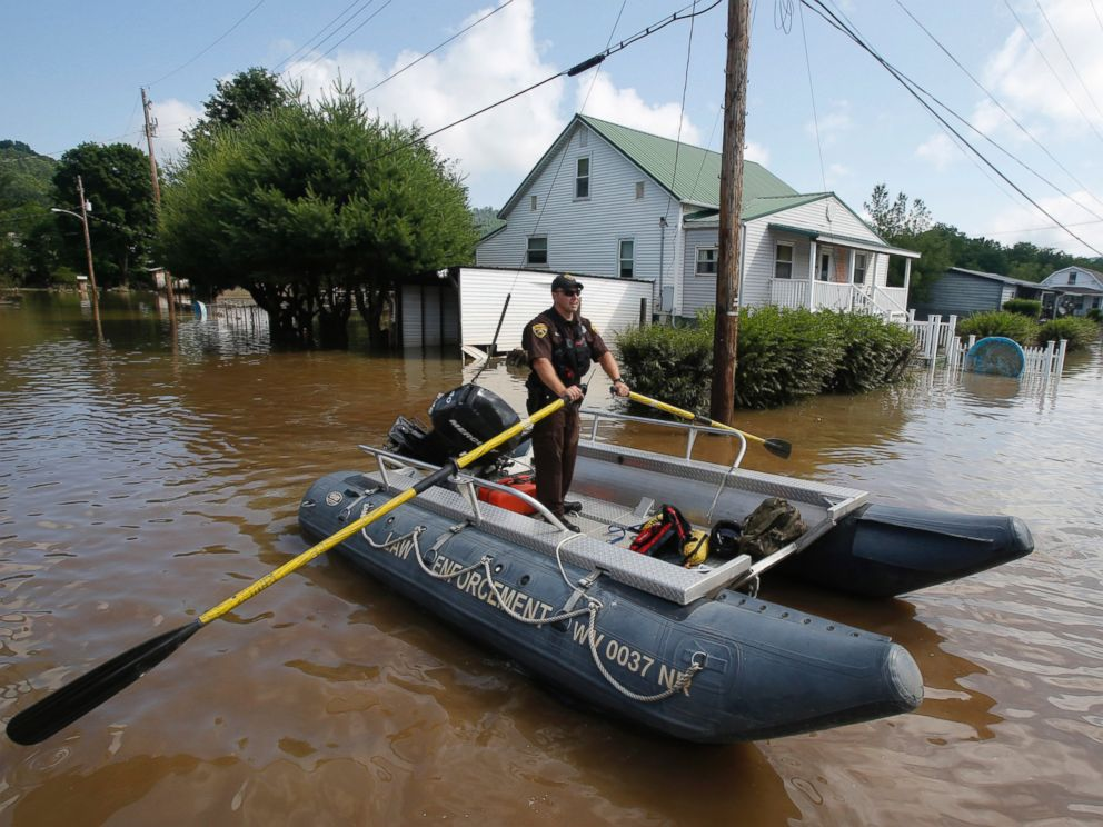 PHOTO: Lt. Dennis Feazell, of the West Virginia Department of Natural Resources, rows his boat as he and a co-worker search flooded homes in Rainelle, W.Va., June 25, 2016.