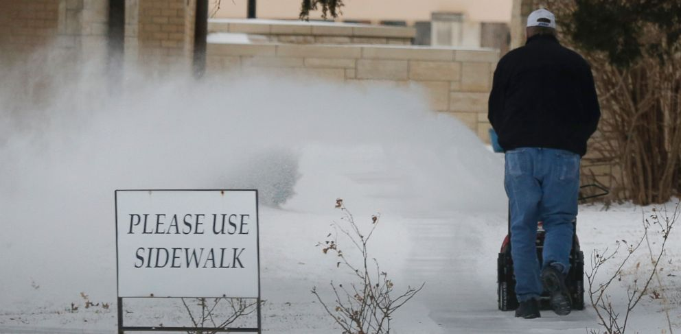 PHOTO: A worker clears snow from a sidewalk at the St. Lawrence Catholic Campus Center near the University of Kansas in Lawrence, Kan., March 2, 2014.