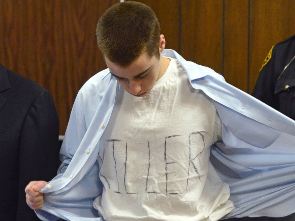 In this Tuesday, March 19, 2013, photo, T.J. Lane unbuttons his shirt during sentencing in Chardon, Ohio. Ohio police said Thursday, Sept. 11, 2014, that Lane, 19, the convicted killer of three students at a high school cafeteria, escaped from prison.