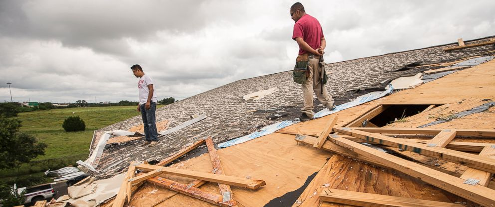 PHOTO: Edgar Mascorro, left, and Emir Nevarez check out the damage on the rooftop at the Silver Springs Apartments in North Austin, Texas, May 24, 2015.