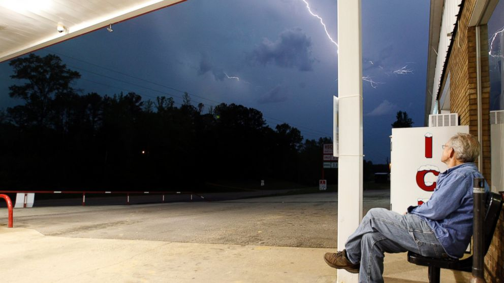 Jimmy Sullinger sits and watches lightning as a storm approaches the gas station where he works, April 28, 2014, in Berry, Ala.