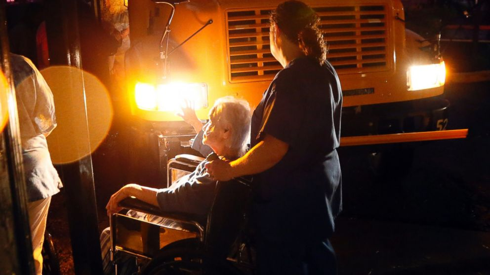 Nursing home personnel assist a resident as she is wheeled to a waiting bus outside a Louisville, Miss., nursing home, April 28, 2014 after the facility and the Winston Medical Center next door were heavily damaged by a tornado.
