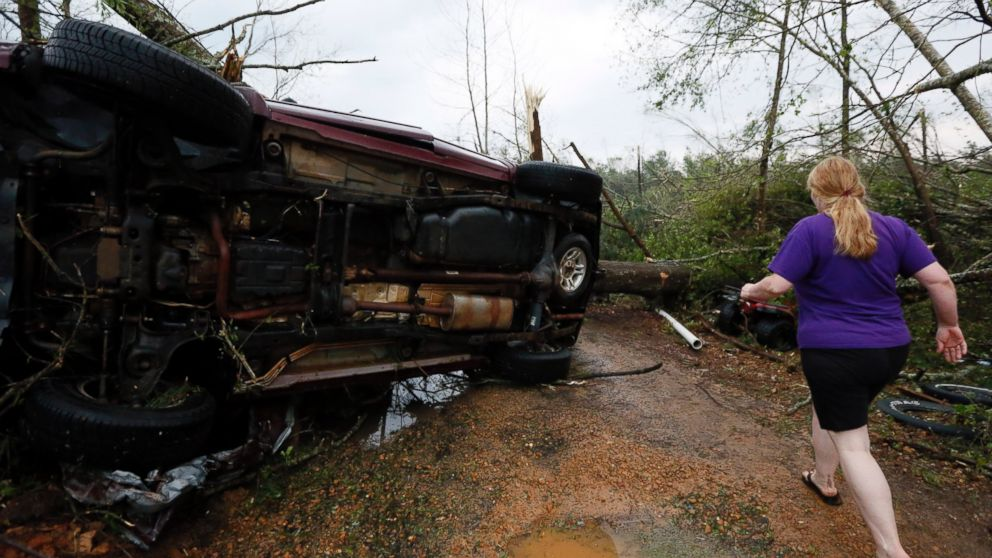 A resident rushes past an SUV that was tossed by a tornado in  Four Corners, Miss., April 28, 2014.