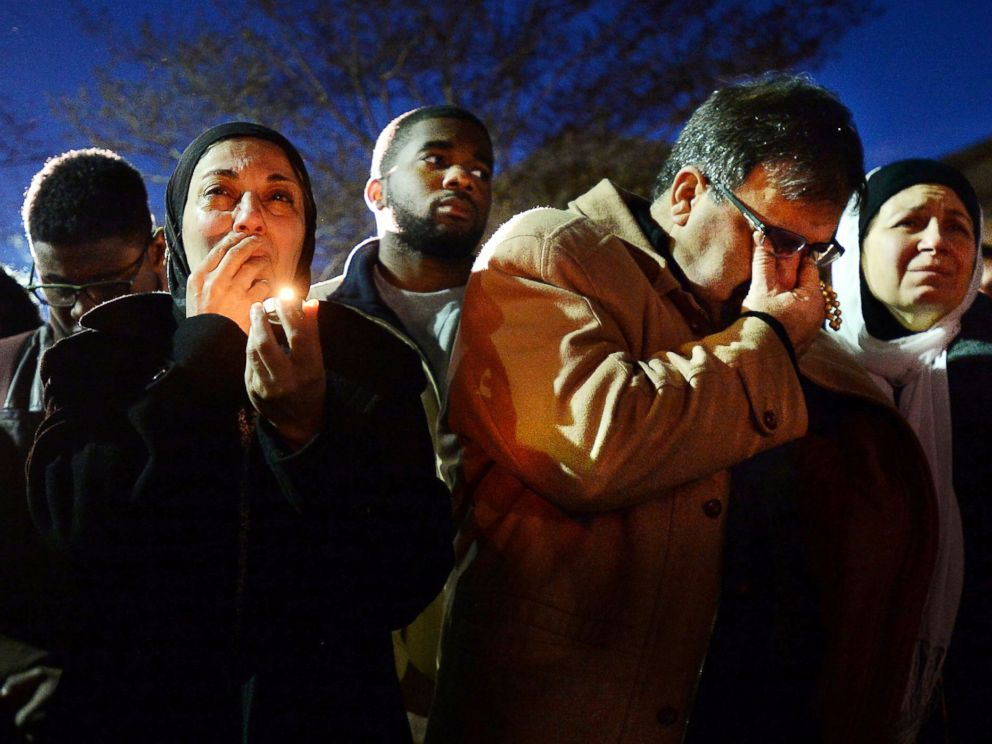 Namee Barakat, right, wipes away tears as he and his wife, Layla, left, watch photos projected on a screen during a vigil for his son, daughter-in-law and her sister, who were killed near UNC-Chapel Hill, Feb. 11, 2015, in Chapel Hill, N.C.