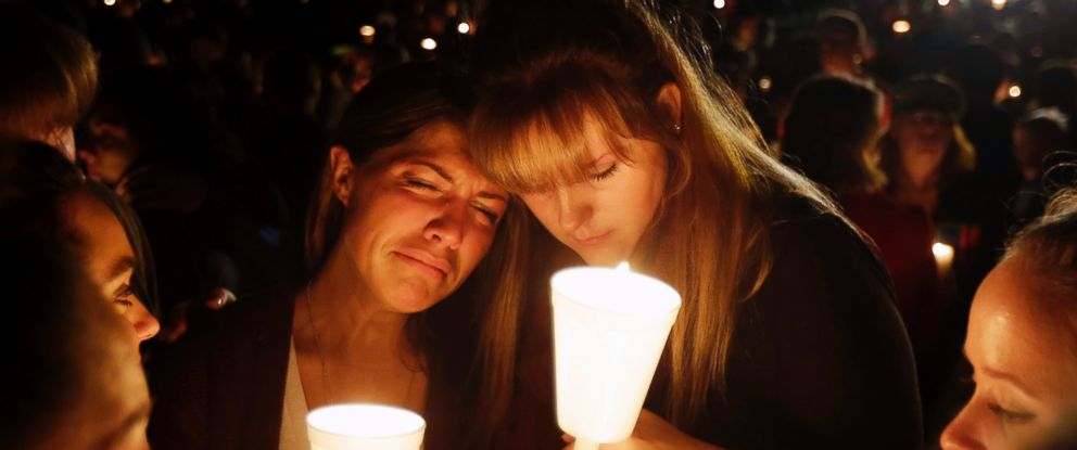 PHOTO: Kristen Sterner, left, and Carrissa Welding, both students of Umpqua Community College, embrace each other during a candle light vigil for those killed during a fatal shooting at the college, Oct. 1, 2015, in Roseburg, Ore.