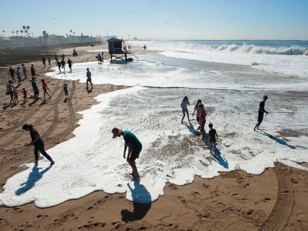 PHOTO: Spectators on the beach scramble as a wave covers the beach in Seal Beach, Calif., Aug. 27, 2014.