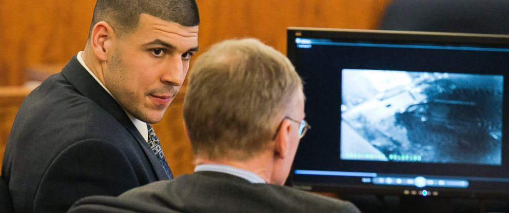 PHOTO: Former NFL player Aaron Hernandez looks at his attorney as security footage plays