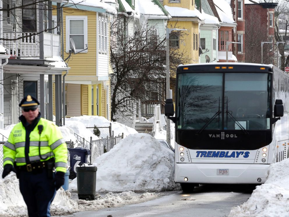 PHOTO: A Massachusetts state police law enforcement official, left, walks near the yellow home, center left, where the late Odin Lloyd lived in Boston, Feb. 6, 2015.