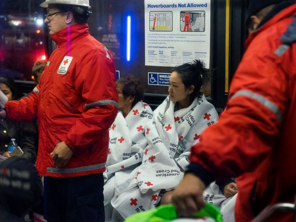 PHOTO: Members of the Red Cross assist people gathering on a city bus, Oct. 27, 2016, after fleeing the area from a fire at an apartment building on the Upper East Side in New York.