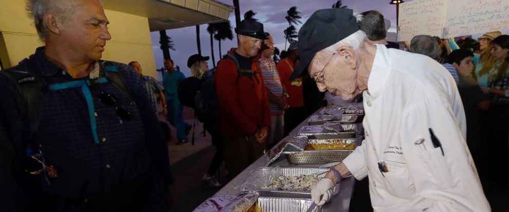 PHOTO: Homeless advocate Arnold Abbott, 90, director of the nonprofit group Love Thy Neighbor Inc., right, serves food to the homeless from a public parking lot next to the beach,Nov. 5, 2014, in Fort Lauderdale, Fla.