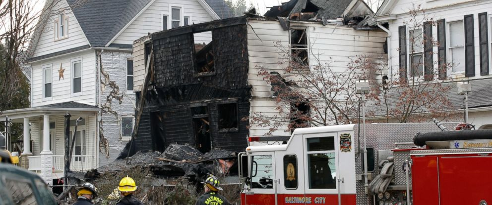 PHOTO: Fire officials stand at the scene of an early morning house fire in Baltimore, Jan. 12, 2017.