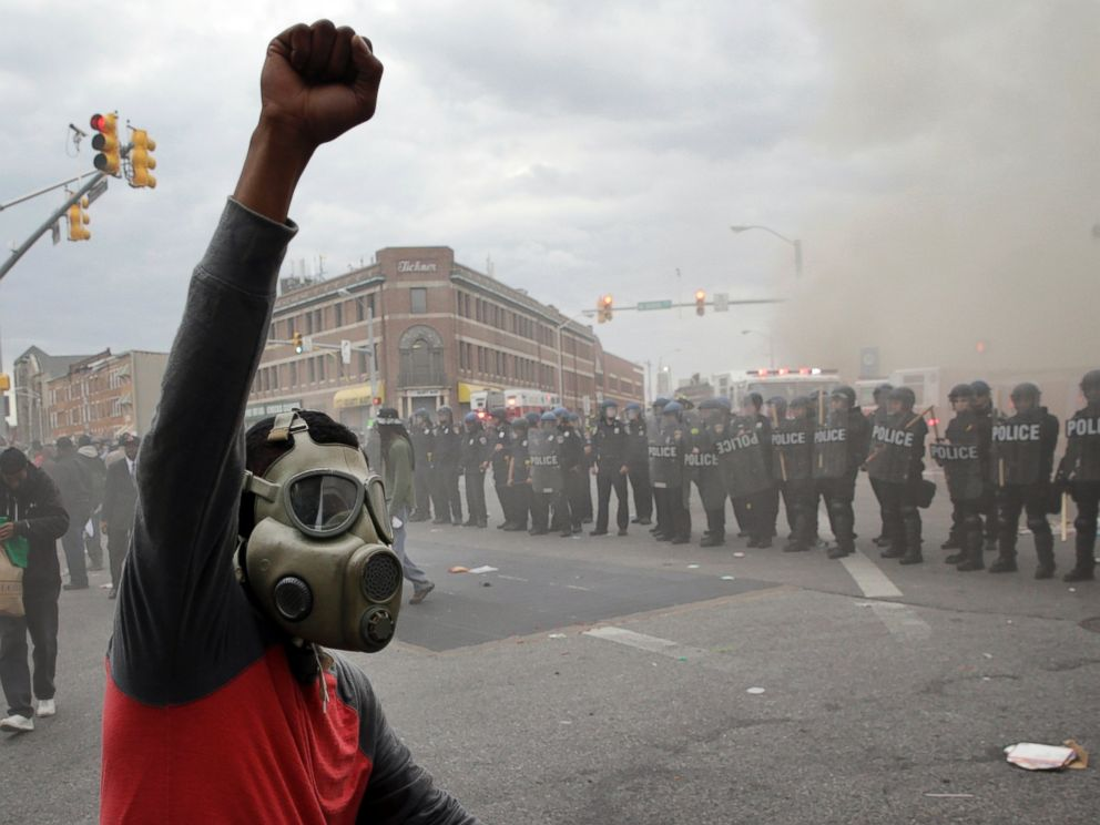 PHOTO: A demonstrator raises his fist as police stand in formation as a store burns, April 27, 2015, in Baltimore.