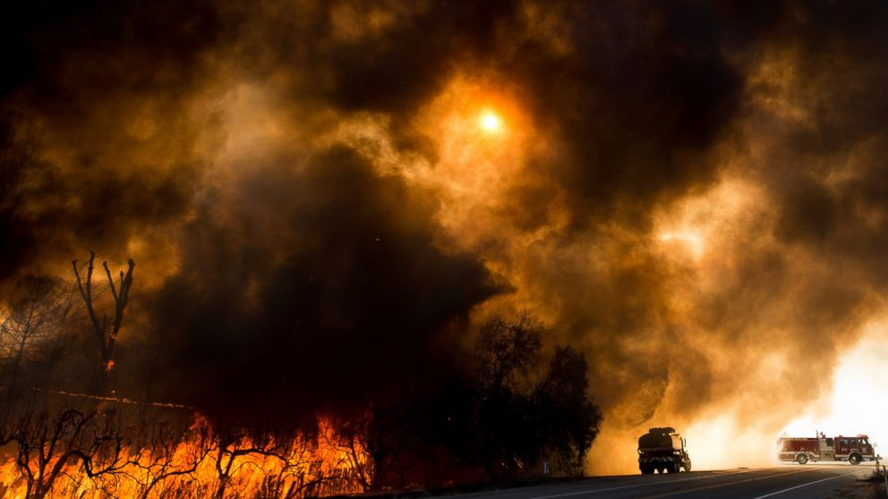Firefighters battle a wildfire as it crosses Cajon Boulevard in Keenbrook, California, Aug. 17, 2016.