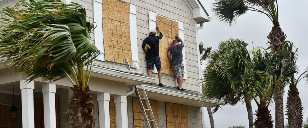 PHOTO: Workers from Armstrong Construction put plywood over windows of a home in preparation for Hurricane Matthew, Oct. 5, in Ponte Vedra Beach, Florida.