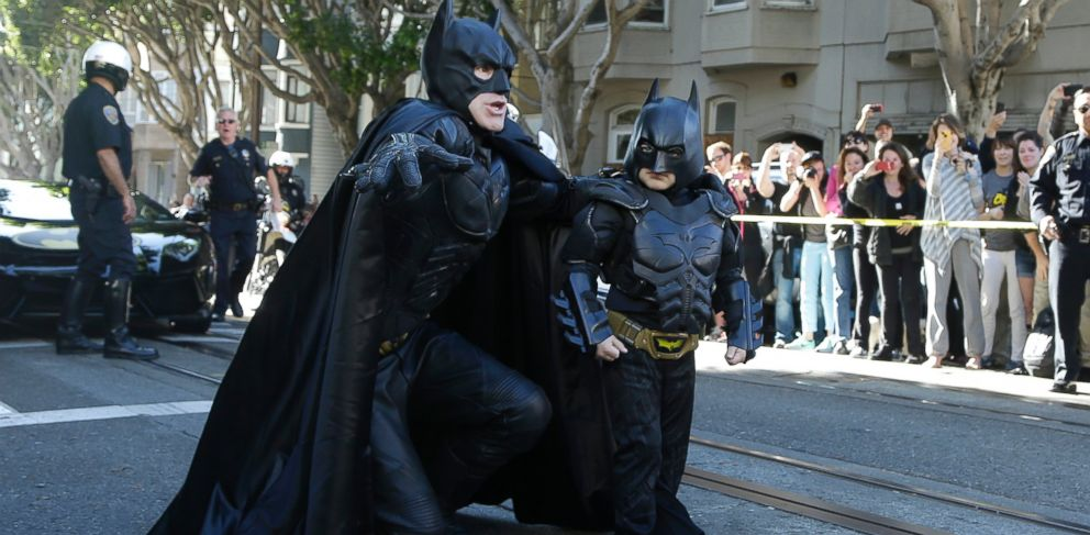 PHOTO: Miles Scott, dressed as Batkid, right, walks with Batman before saving a damsel in distress in San Francisco, Nov. 15, 2013.