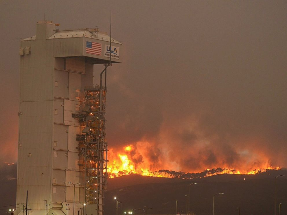 PHOTO: In this Monday, Sept. 19, 2016 photo provided by the Santa Barbara County Fire Department, a fire burns several miles behind Space Launch Complex-3, housing the Atlas V rocket & WorldView 4 satellite, at Vandenberg Air Force Base, California.