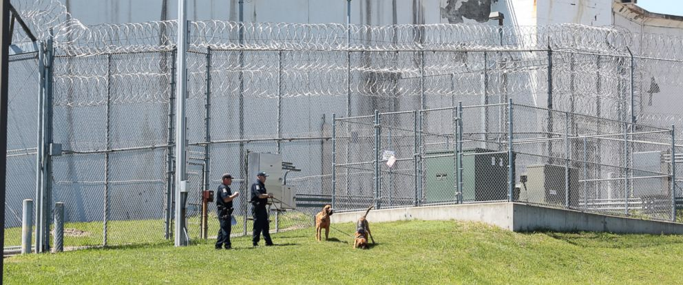 PHOTO: Law enforcement officers with bloodhounds stand guard at one of the entrances to the Clinton Correctional Facility in Dannemora, N.Y. on Saturday, June 6, 2015.