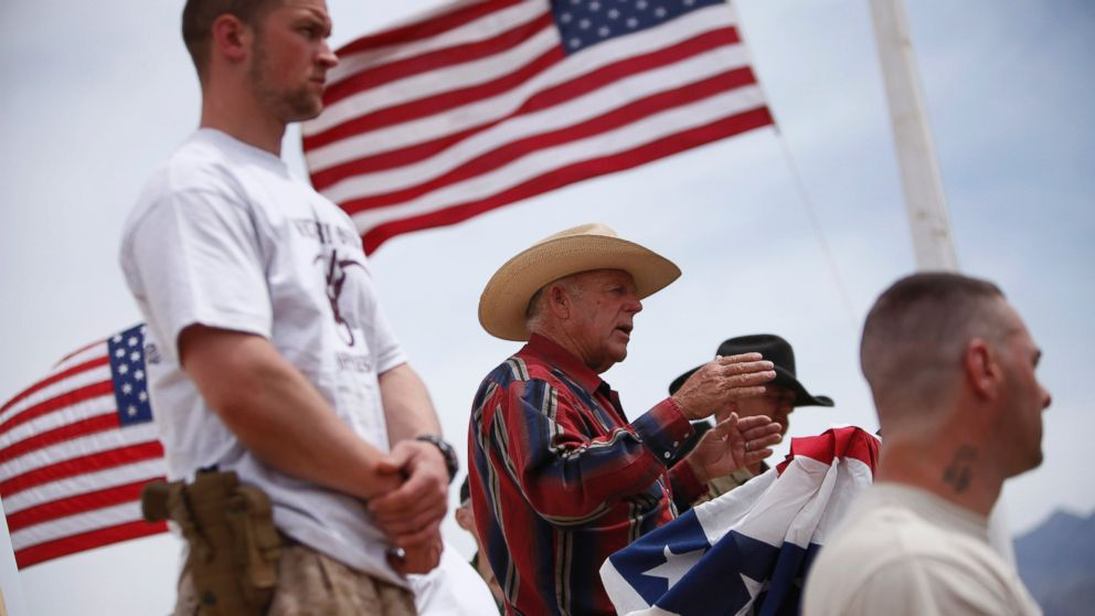 Flanked by armed supporters, rancher Cliven Bundy speaks at a protest camp near Bunkerville, Nev. Friday, April 18, 2014.