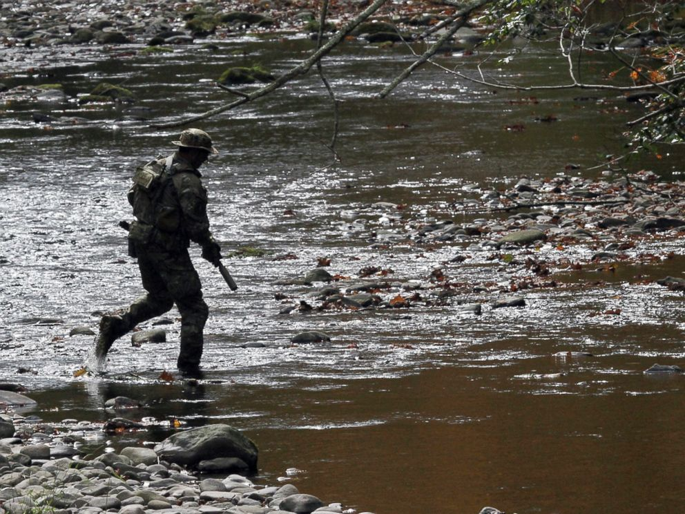 PHOTO: A U.S. marshal patrols along Mill Creek near Clarks Road in Barrett Township, Pennsylvania, Sept 29, 2014, during the search for Eric Frein.