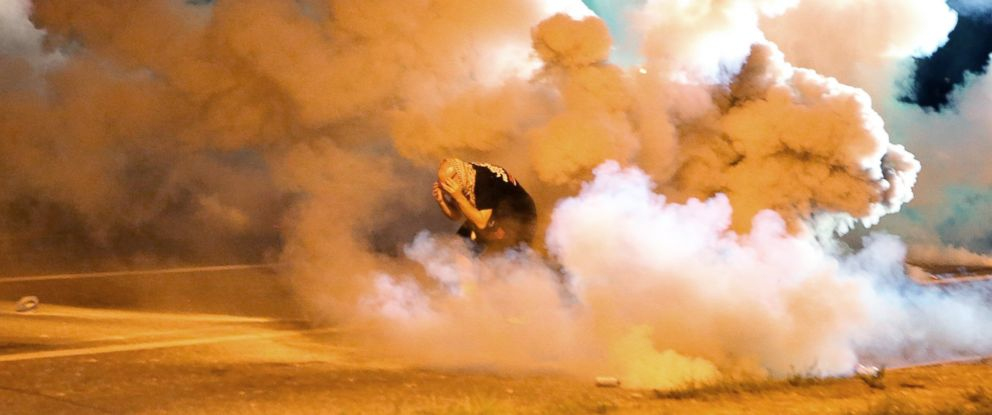 PHOTO: A protester takes shelter from smoke billowing around him, Aug. 13, 2014, in Ferguson, Mo.