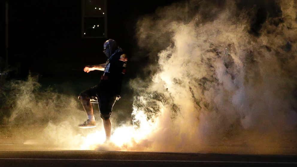 A protester kicks a smoke grenade that had been deployed by police back in the direction of police, Aug. 13, 2014, in Ferguson, Mo.