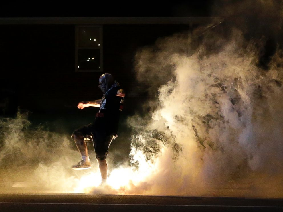 PHOTO: A protester kicks a smoke grenade that had been deployed by police back in the direction of police, Aug. 13, 2014, in Ferguson, Mo.