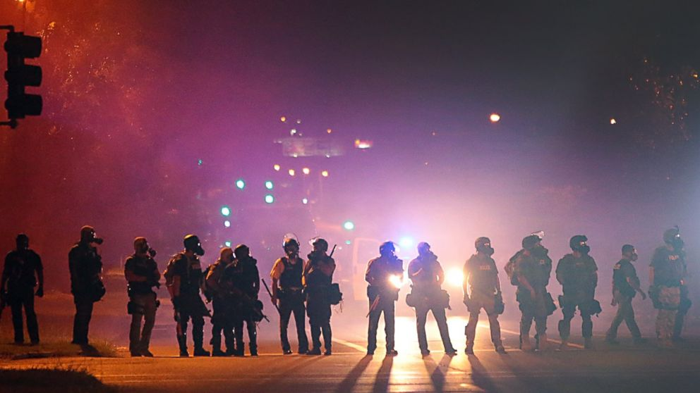 Police officers work their way north on West Florissant Avenue in Ferguson, Mo., clearing the road of people, Aug. 13, 2014.