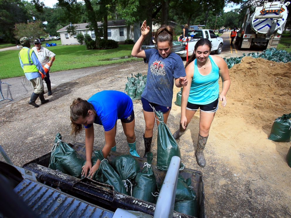 PHOTO: Volunteers from Teurlings Catholic High School add sandbags to a tractor loader as volunteers place sandbags near a levy located in the River Oaks neighborhood in Lafayette, Louisiana, Aug. 15, 2016.