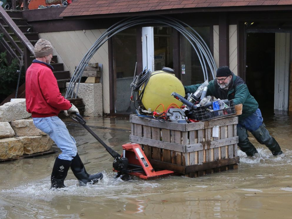 PHOTO: Mark Diehl, left, and Dale Atchley move items to higher ground at the Fenton Feed Mill, Dec. 29, 2015, in Fenton, Mo.