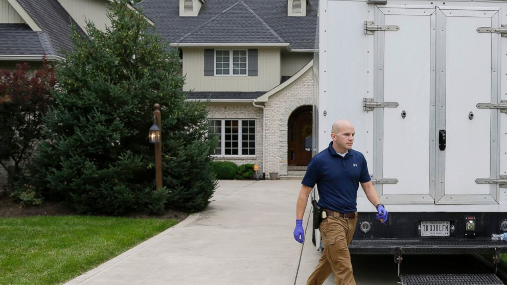 Federal authorities walk outside of the home of Subway restaurant spokesman Jared Fogle, July 7, 2015, in Zionsville, Ind.