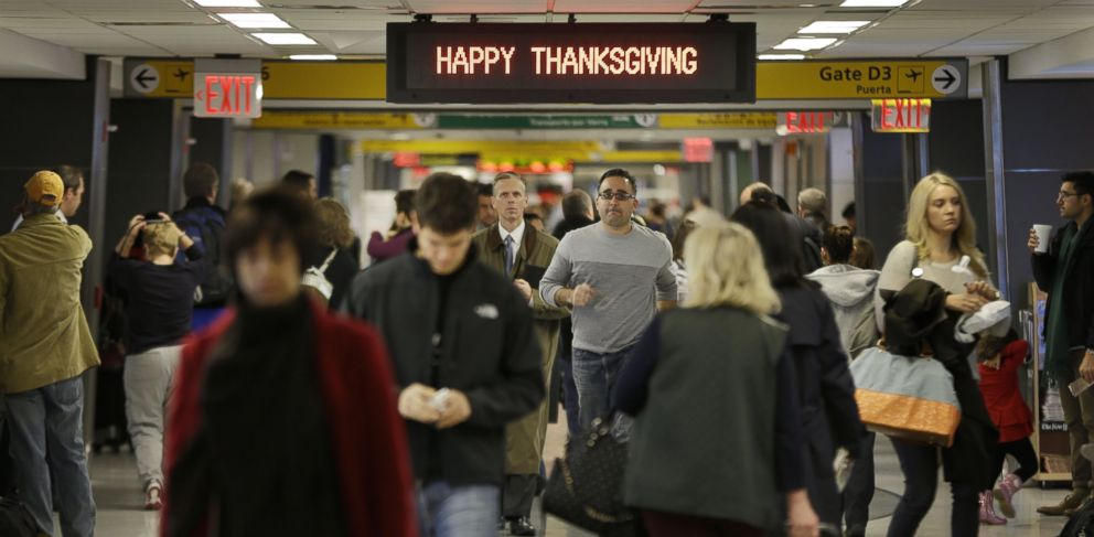 """PHOTO: Travelers walk under a sign reading """"Happy Thanksgiving"""" at LaGuardia Airport in New York, Nov. 26, 2013."""