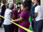 PHOTO: A hospital worker views police activity near the scene of a shooting at a wellness center attached to Mercy Fitzgerald Hospital in Darby, Pa., July 24, 2014.