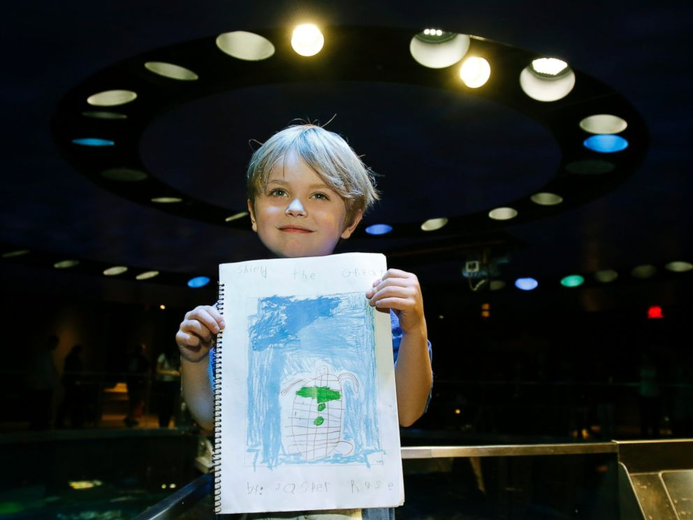 PHOTO: Jasper Rose, of Watertown, Mass., holds a booklet he created about turtles as he stands by the main tank at the New England Aquarium, April 22, 2016, in Boston.