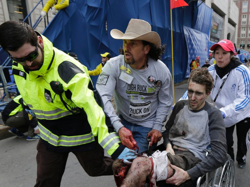 PHOTO: Boston Marathon bombing survivor Jeff Bauman is helped by Emergency Medical Services EMT Paul Mitchell, left, Carlos Arredondo, center, and Devin Wang, right, after he was injured in one of two explosions in Boston, April 15, 2013.