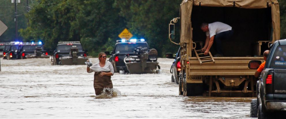 PHOTO: Jeff Robinson lowers a ladder from a Louisiana National Guard truck as his wife wades through flood waters from the Natalbany River near their home in Baptist, Louisiana, Aug. 13, 2016.